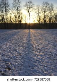 An empty, snowy baseball field in winter