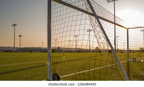 Empty Soccer Field With Goalpost Against Sunset, Stadium Lights In Sight