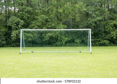 Empty soccer field with green grass. Goal with net. Nature in the background. Concept of summer leisure and sport.