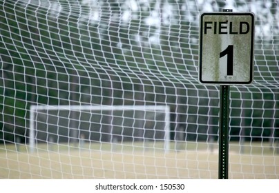 empty soccer field - view through the net with a sign that says Field 1