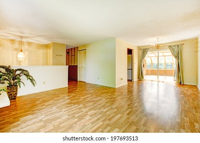 Empty soft colors empty living room with shiny hardwood floor and walkout screened deck