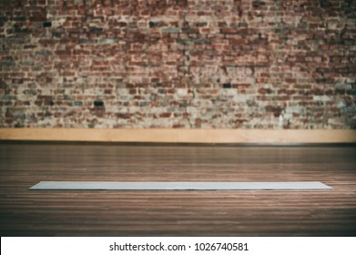 Empty space in fitness center, brick wall, natural wooden floor, modern loft studio, unrolled yoga mat on the floor. no people.