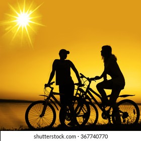 Empty Space. friends on bicycle on sunset. Silhouette couple cyclist stand along shoreline coast. Sport in Nature background. Group of people. two biker in sunrise with reflection sun in water