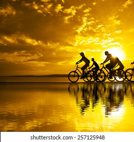 Empty Space for inscription Sporty company friends on bicycles outdoors sunset Silhouette five 5 cyclist going along shoreline coast Reflection sun on water Sport in Nature background Group of people