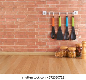Empty space on the kitchen counter with utensils on hooks against brick wall