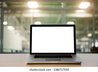 Empty space on wooden Desk with Laptop with blank white screen,In office blurred background of bokeh. - Image