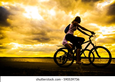 Empty Space. Sporty friends on bicycle on sunset. Silhouette couple cyclist go along coast. Sport in Nature background. Group of people two mountain biker in sunrise with reflection sun in water