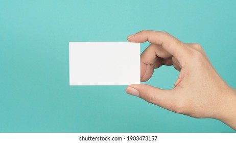 Empty space for text.Male hand holding white blank card isolated on green or Tiffany Blue background.