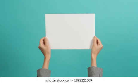 Empty space for text.Woman hands holding blank paper and wear grey suit isolated on blue and green background.