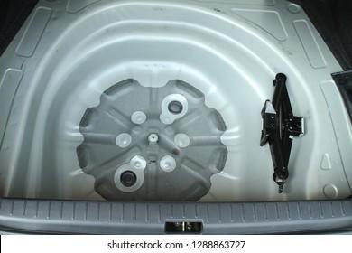 Empty spare wheel storage bin in a car