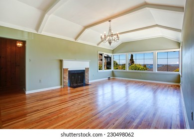 Empty specious living room interior with vaulted ceiling, light mint walls, hardwood floor and fireplace. Room with bay view