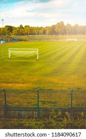 Empty sports field in the glow of the evening sun with distant open air stadium seating and white goalposts on neat green grass