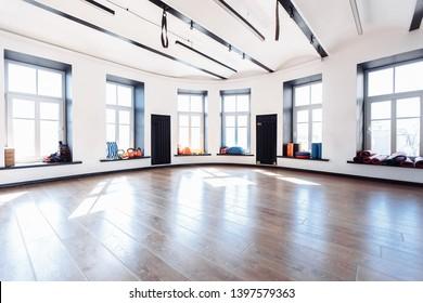 Leere Sporthalle mit großen Fenstern und Sportgeräten für sportliche Aktivitäten. Yoga- und Dehnungskonzept