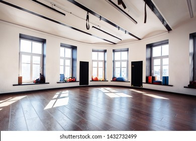 Empty sports gym with large windows and sports equipment in anticipation of sports activities. Yoga and stretching concept