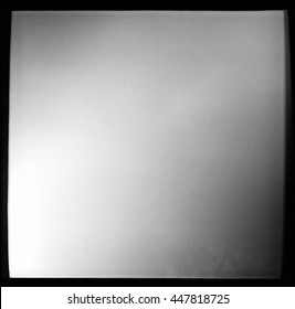 Empty square black and white film frame with heavy grain and light leak