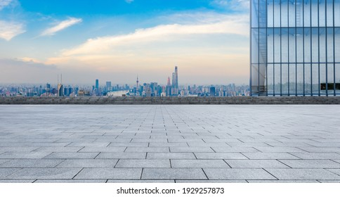 Empty square floor and city skyline with buildings at sunset in Shanghai.