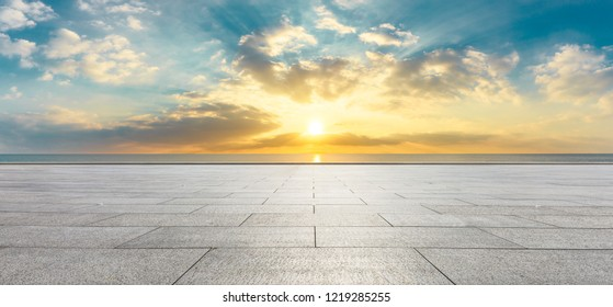 Empty square floor and dramatic sky with coastline panorama at sunset