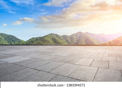 Empty square floor and green mountain natural landscape at sunset