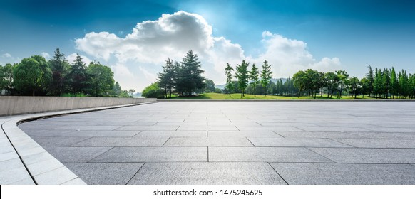 Empty square floor and green woods natural scenery in city park - Shutterstock ID 1475245625