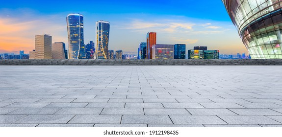 Empty square floor and modern city skyline with buildings in Hangzhou at night.