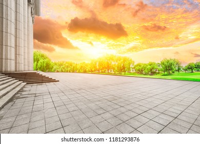 Empty square floor and modern urban architecture at sunset