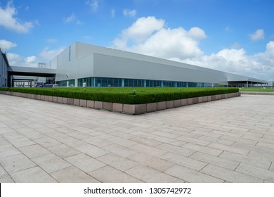 Empty square floor tiles and modern factory buildings and wareho