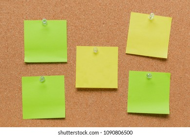 empty square green and yellow pinned sheet on a brown cork reminder