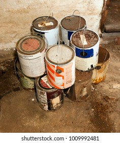 Empty stacked paint cans on dirty basement floor.