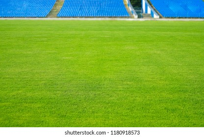 Empty stadium. front view . soccer field - green grass field and arena seats.