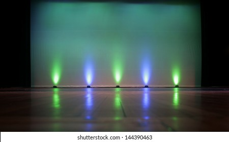 Empty Stage with a Blank Screen, highlighted by colorful stage lighting. Plenty of empty screen space for copy text.