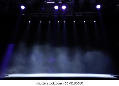 An empty stage, lit by spotlights and smoke before the performance