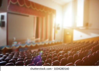 Empty stage at theatre hall for ted talk show, seminar audience, musical or educational with morning sun light blur image use for background.