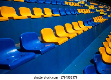 Empty stands, tribune with several raws of plastic blue and yellow seats, chairs for fans at a sport stadium.