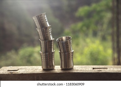 Empty steel glasses on one another.  local people in Indian rural villages using it to drink hot tea. kept on old wooden table, India