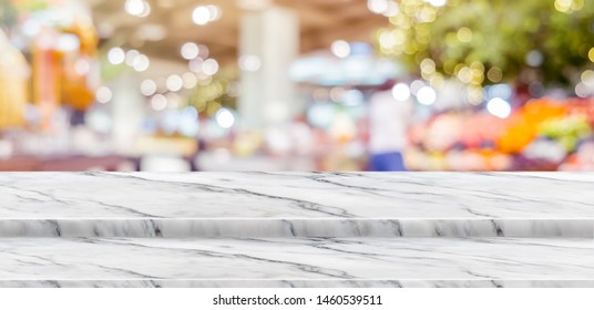 Empty step white marble table top food stand with blur supermarket background bokeh light,Mock up for display or montage of product,Banner for advertise on online media,business presentation