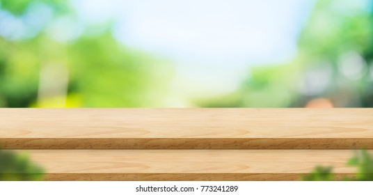 Empty step wood table top food stand with blur green park background and blurred leaf at foreground bokeh light,Mock up for display or montage of product,Banner for advertise on online,nature store