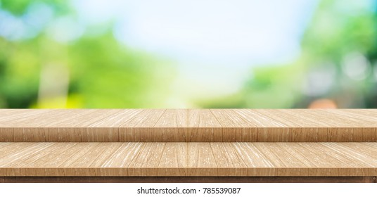Empty step wood table top food stand with blur green park tree background bokeh light,Mock up for display or montage of product,Banner for advertise on online media,nature business presentation