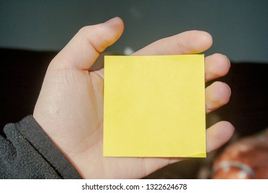 Empty sticky note in human fingers. Blank in hand on dark background
