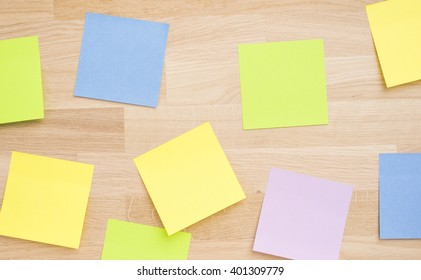 Empty sticky notes on wooden table. Office desktop background with copy space.