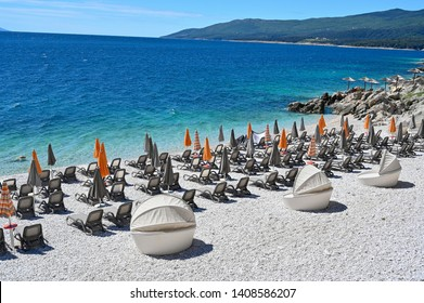 empty stone beach with sunshades in Rabac Croatia
