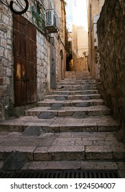 Empty stone paved alley in Old Town Jerusalem, staircase and old buildings