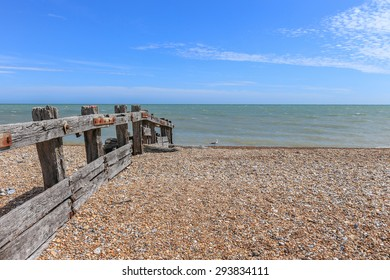 An empty stoney beach with weathered and rusty wooden groynes, on the English coastline.