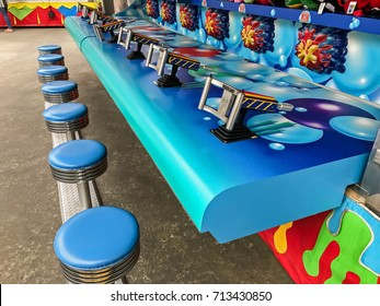 Empty stools at an arcade game where people are shooting water into a small hole competing to win a stuffed animal.