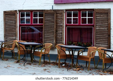 Empty street cafe in european old town. Belgium, Brugge (Bruges). Empty tables and chairs against old white brick building with open shutters and red window curtains. Fallen dry leaves in winter cafe.