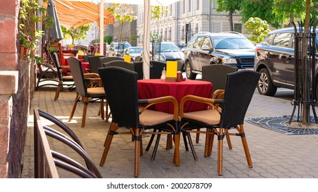 An empty street cafe with no people during the coronavirus pandemic. A cozy table with a red tablecloth in a small cafe without visitors in the morning.