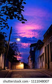 Empty street of city Santiago de Cuba with amazing night sky colored in blue and pink colors