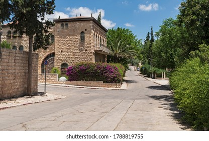 an empty street in the historic yemin moshe neighborhood of jerusalem during the coronavirus pandemic of 2020 showing ancient limestone buildings and the edge of a park