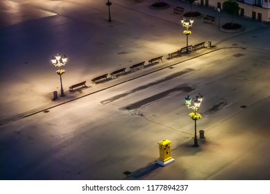 An empty street with a mailbox and street lamps