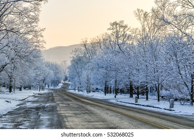 An empty street makes its way towards the snowy green mountains in Brandon, Vermont.