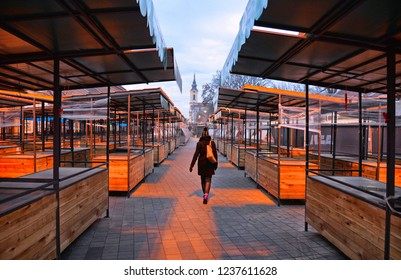 empty street market in the end of day in Zemun Belgrade with lonely woman walking and old church tower in background, Serbia